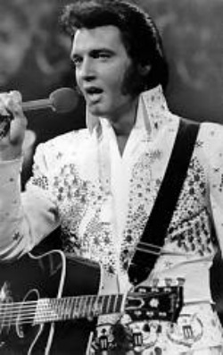 Go to Elvis Biography, read the story and watch Elvis in concert.
